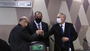 Dimas Covas, presidente do Butantan, cumprimenta Renan Calheiros com um soquinho, enquanto Omar Aziz, entre os dois, assiste à cena com aparente sorriso; todos estão de terno, gravata e máscara