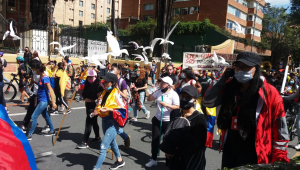 Pessoas nas ruas manifestando com bandeiras em forma de pomba em Bogotá, na Colômbia