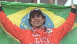 Andre Ribeiro de uniforme vermelho da Fórmula 1, boné preto, sorrindo e segurando uma bandeira do Brasil