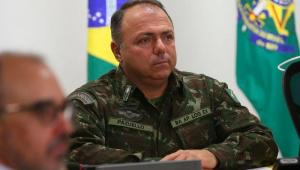 Vestido com roupa militar, o general Eduardo Pazuello aparece sentado atrás de uma mesa, com uma bandeira do Brasil atrás dele