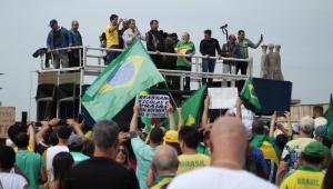 Jair Bolsonaro e outras pessoas em cima de um trio elétrico. Na foto, aparecem várias bandeira do Brasil e um público com camisetas e bandeiras