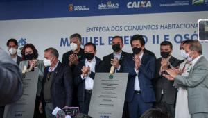 Doze políticos, entre eles Carla Zambelli (a única mulher, do lado esquerdo da imagem), Rogério Marinho (do lado direito da deputada), João Doria (no centro da foto) e Ricardo Nunes (perto de Doria, à direita), se apertam em palco durante inauguração de conjunto habitacional