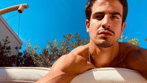 Enzo Celulari, homem de cabelos castanhos pretos e bigode, deitado em cima de uma poltrona e tirando uma selfie