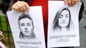 Uma mulher segura um retrato do jornalista da oposição Roman Protasevich e sua namorada Sofia Sapega durante um protesto de solidariedade a Roman Protasevic na embaixada da Bielo-Rússia em Riga, Letônia