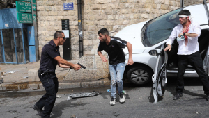 Policial israelense (esquerda) aponta arma para palestino (centro) ao lado de um judeu ortodoxo ferido (direita) em Jerusalém