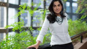 Mulher com cabelos pretos apoiada em um corrimão com uma blusa branca, calça preta e colar preto. Atrás, um cenário de uma janela com várias plantas