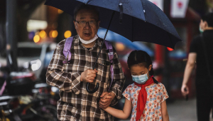 Senhor idoso segura a mão de menina antes de atravessarem a rua na China