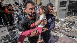 Homem carrega criança no colo em lugar destruído