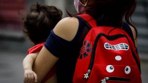 Imagem de uma mulher com uma mochila vermelha infantil segurando uma criança