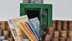 Imagem mostra notas de R$ 50, de R$ 20 e de R$ 5 saindo de um cofre entreaberto e moedas empilhadas ao redor e em cima do objeto