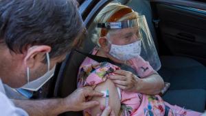 Idosa recebendo dentro da carro a vacina contra a Covid-19