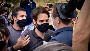 Jairinho, que assassinou o menino Henry Borel, com uma multidão em volta. Ele usa camisa polo preta e máscara de proteção.