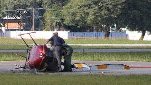 Dois homens vistoriam um helicóptero vermelho que caiu na pista do Campo de Marte