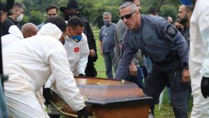 pessoas enterrando um caixão, algumas com trajes de proteção à Covid-19
