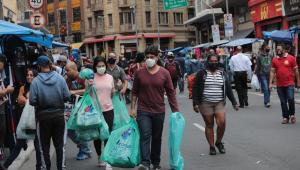 Pessoas andam pela 25 de março carregando sacolas de compras