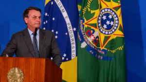 O presidente Jair Bolsonaro fazendo pronunciamento em frente à bandeira do Brasil e da República