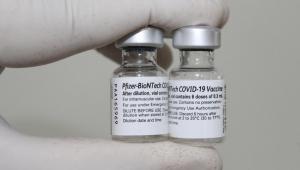 Mão de enfermeiro com luvas segura frascos da vacina da Pfizer