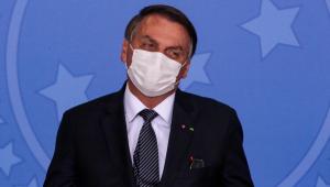 O presidente da República, Jair Bolsonaro, usa máscara de proteção branca e veste terno preto durante evento oficial