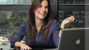 Mulher rindo em frente a um notebook. Ela é branca, tem cabelos castanhos longos e lisos e está com uma camisa azul marinho com bolinhas brancas.
