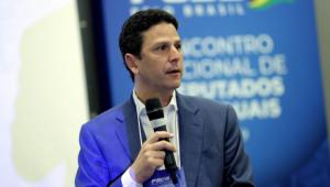 Imagem de Bruno Araújo, presidente nacional do PSDB, segurando um microfone durante evento do partido