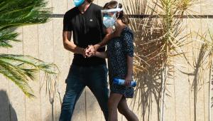 De mãos dadas e máscaras de proteção, Rafael Vitti e Tatá Werneck caminham no cemitério onde Paulo Gustavo foi velado