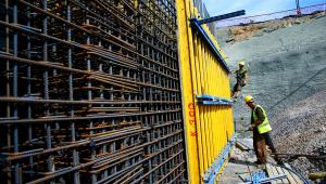 Dois homens construindo uma parede de aço com roupas de obra. Um está em cima da parede e o outro no chão. Uma parte da parede é pintada de amarelo.