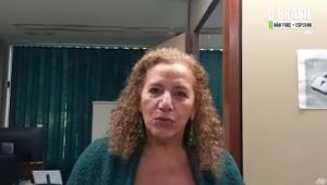 Jandira Feghali grava depoimento à Jovem Pan; ela é morena clara, tem 64 anos e seu cabelo é castanho e encaracolado