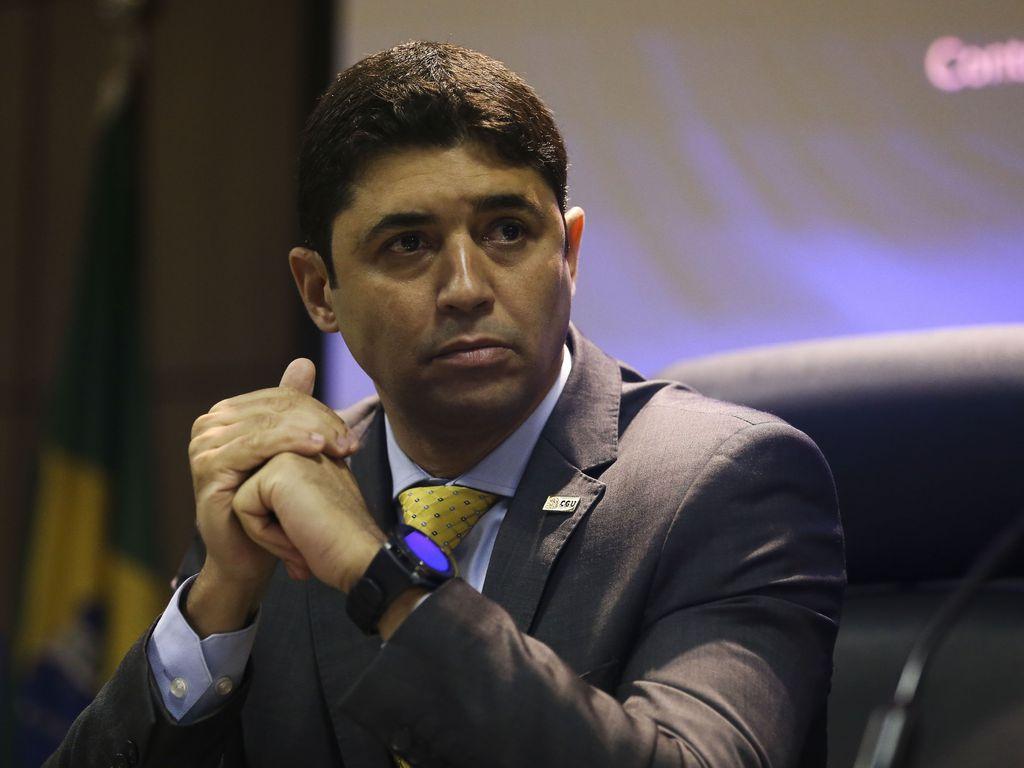 Homem com as mãos juntas sentado olhando para o horizonte. Ele usa terno cinza, tem cabelos curtos e castanhos, uma gravata amarela e um relógio preto.
