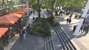 Espaço público em três níveis; na base, um restaurante de dois andares, com mesas cobertas por toldos vermelhos na entrada; no segundo nível, um estreito corredor; mais alto, um largo espaço cimentado; duas árvores compõem a paisagem, e dezenas de pessoas ocupam o lugar