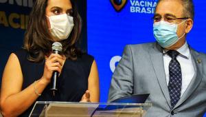 A médica infectologista Luana Araújo ao lado do ministro da Saúde, Marcelo Queiroga, ambos usam máscaras e Luana segura um microfone