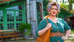 """Cena do filme """"Minha Mãe é Uma Peça"""" mostra Paulo Gustavo vestido como Hermínia, com um vestido verde, maquiagem e bobs no cabelo"""