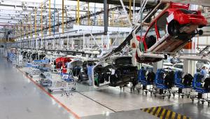 carros sendo montados em fábrica