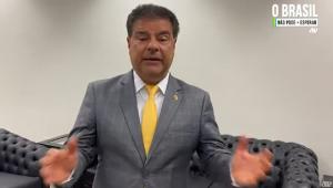 Vestido com terno cinza, camisa branca e gravata amarela, o senador Nelsinho Trad (homem branco de 59 anos, baixo, fora do peso ideal e de cabelo liso, preto, mas com alguns frios brancos), gesticula em pé enquanto fala em uma sala decorada com dois sofás
