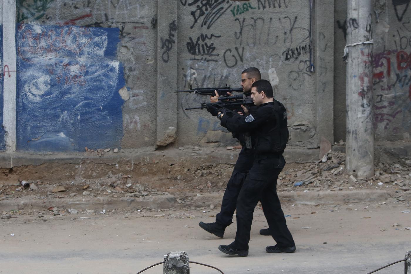 dois policiais com fardas pretas apontando armas