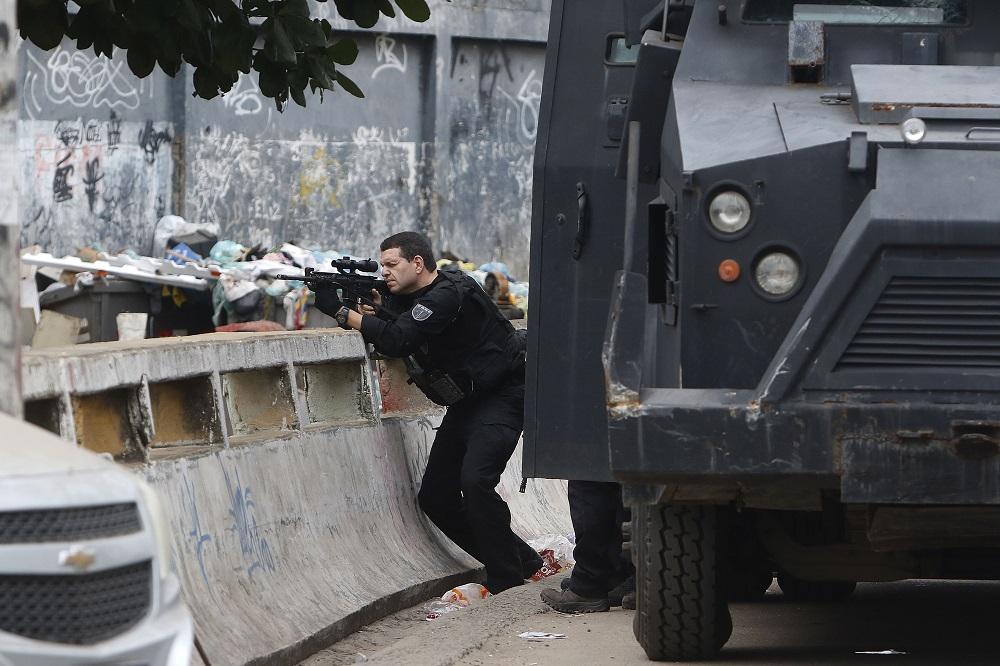Ao lado do blindado, policial se esgueira sobre parapeito na favela e aponta o seu fuzil