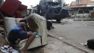 Em favela do Rio, morador se esconde atrás de sofá velho na calçada enquanto caveirão da polícia passa pela rua