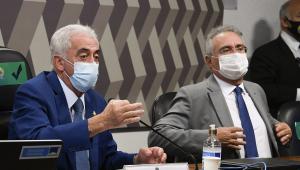 Dois senadores de máscara na mesa da presidência da CPI