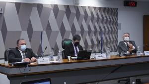 Bancada da CPI da Covid mostra sentados lado a lado, Eduardo Pazuello, Randolfe Rodrigues e Renan Calheiros, todos com trajes sociais
