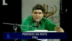 """TV exibe trecho de """"Perdidos da Noite"""", com o apresentador Fausto Silva falando em frente a um microfone postado em cima de uma mesa"""