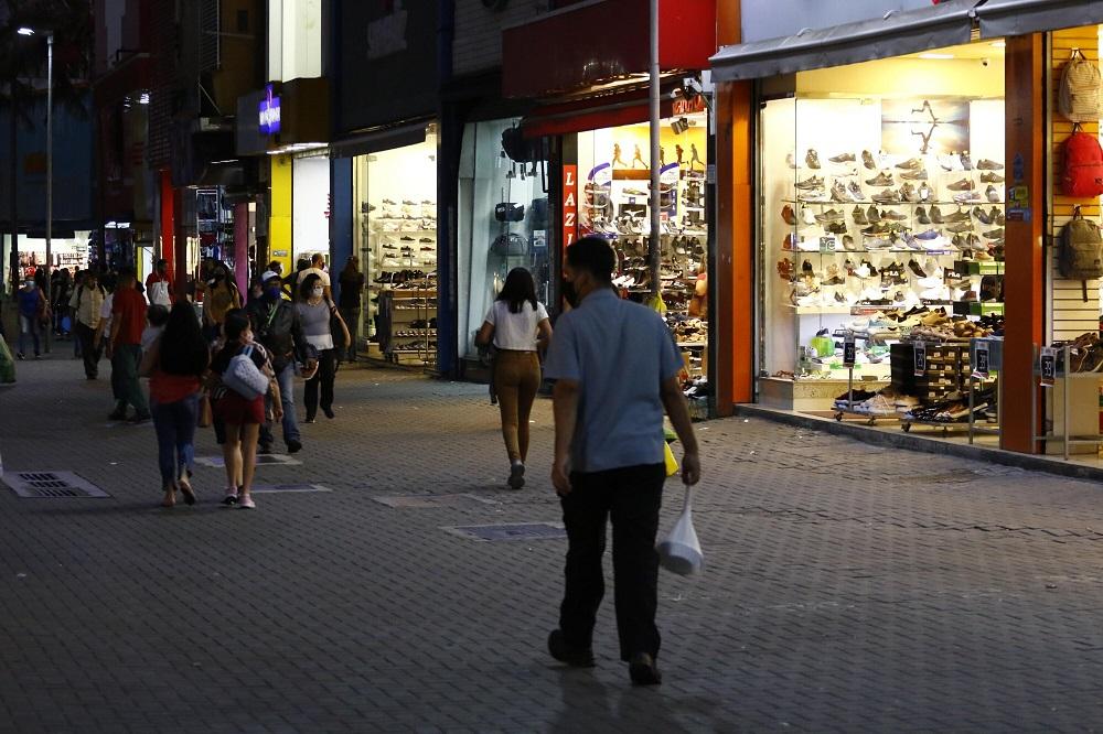 Com lojas abertas, a maioria de calçados, pessoas circulam à noite em calçada do centro de São Paulo
