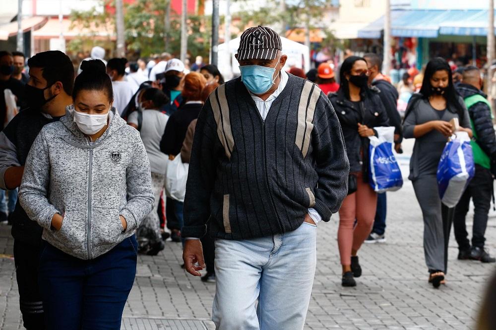 Dezenas de pessoas com máscaras de proteção e roupas de frio transitam por uma larga calçada em São Paulo