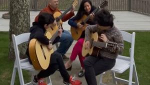 Quatro pessoas sentadas tocando violão