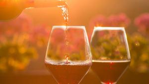 Vinho sendo servido em uma taça e outra taça ao lado, já com metade do copo com o líquido
