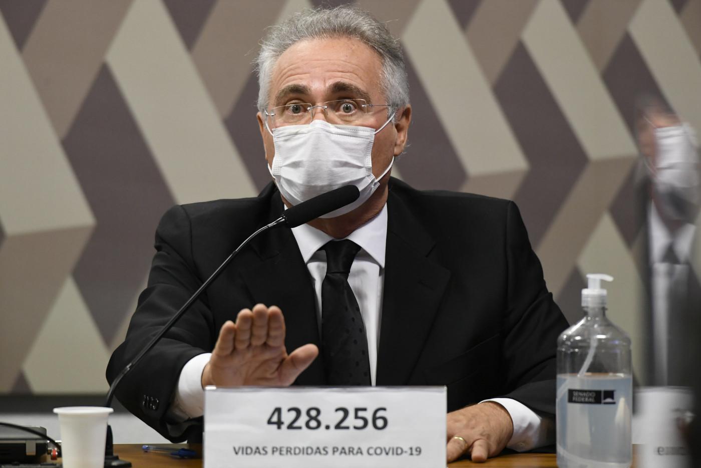 senador renan calheiros falando, com a mão levantada, em frente a um microfone. Ele é branco, tem cabelos grisalhos e usa óculos.