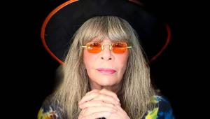 De chapéu preto, óculos laranja, cabelo loiro até o ombro e cruzando as mãos, Rita Lee posa para foto