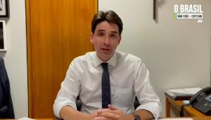 De camisa branca e gravata azul, o deputado Silvio Costa Filho (um homem branco, magro, de cabelo liso preto e 39 anos) cruza as mãos enquanto fala à Jovem Pan