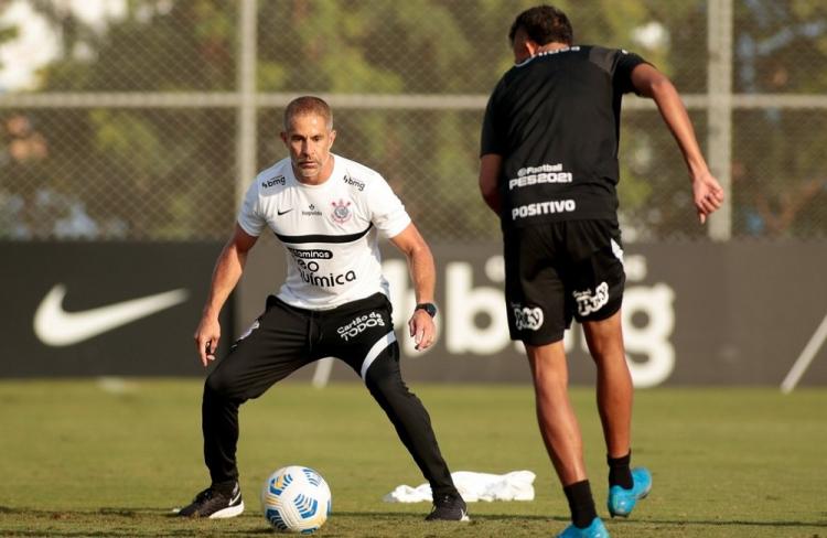 Posicionado com as pernas abertas, de calça de moletom e camisa de treino do Corinthians, Sylvinho participa de atividade com bola junto a outro integrante da comissão técnica