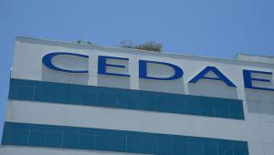 Fachada do edifício-sede da Cedae. Cedae escrito em azul claro e edifício branco