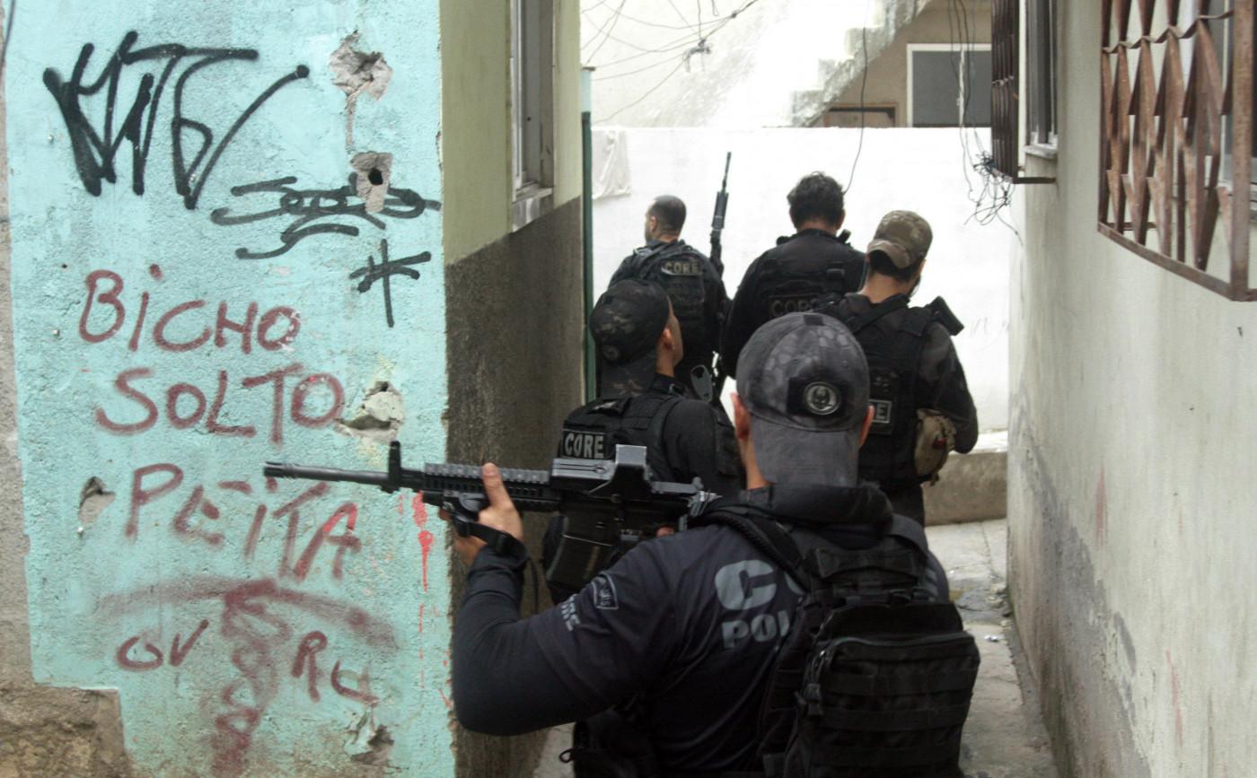 Grupo de policiais com coletes pretos e bonés empunhando armas dentro de uma favela