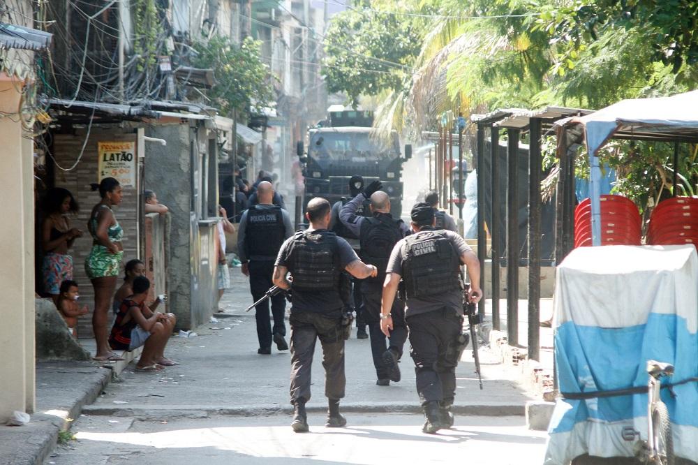 Em uma rua estreia da favela do Jacarezinho, cinco policiais civis andam pela rua, enquanto o caminhão blindado da polícia anda em direção a eles; três crianças e duas mulheres assistem a tudo da calçada